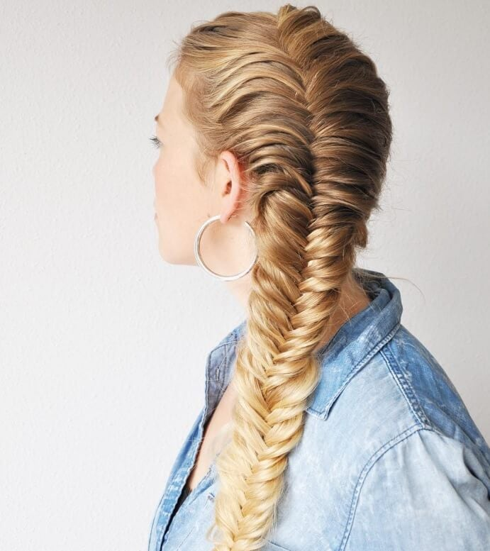 French braid styles: young blonde woman with a French-fishtail braid hybrid