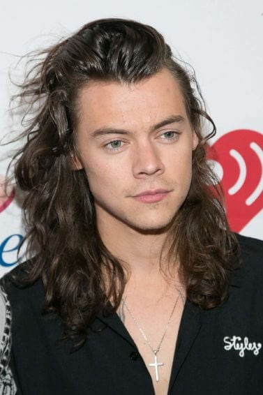 A-list men's long hairstyles: Red carpet shot of Harry Styles with long brown wavy hair pushed back and swept to one side