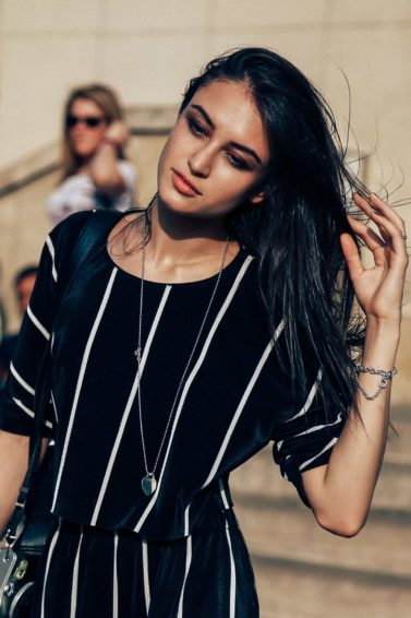 bruentte street styler with glossy hair swept to one side wearing an all in one stripe jumpsuit