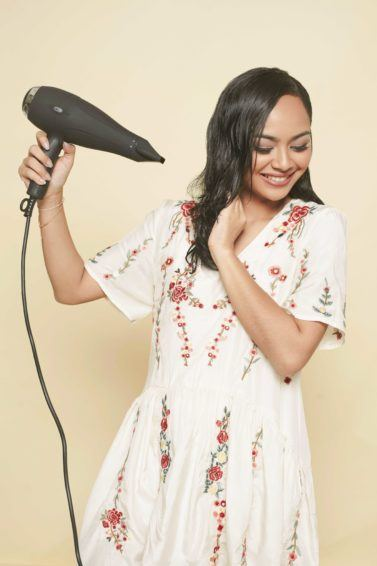 travel hair dryer: close up shot of model holding a hair dryer, wearing a boho dress and posing in a studio