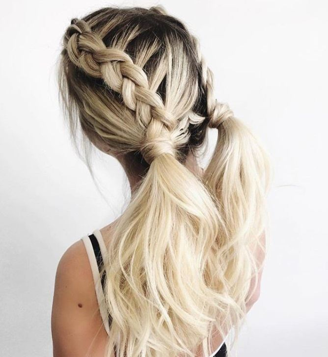 Updos with braids: Back shot of a woman with bleach blonde hair styled into Dutch braid pigtails into ponytails.