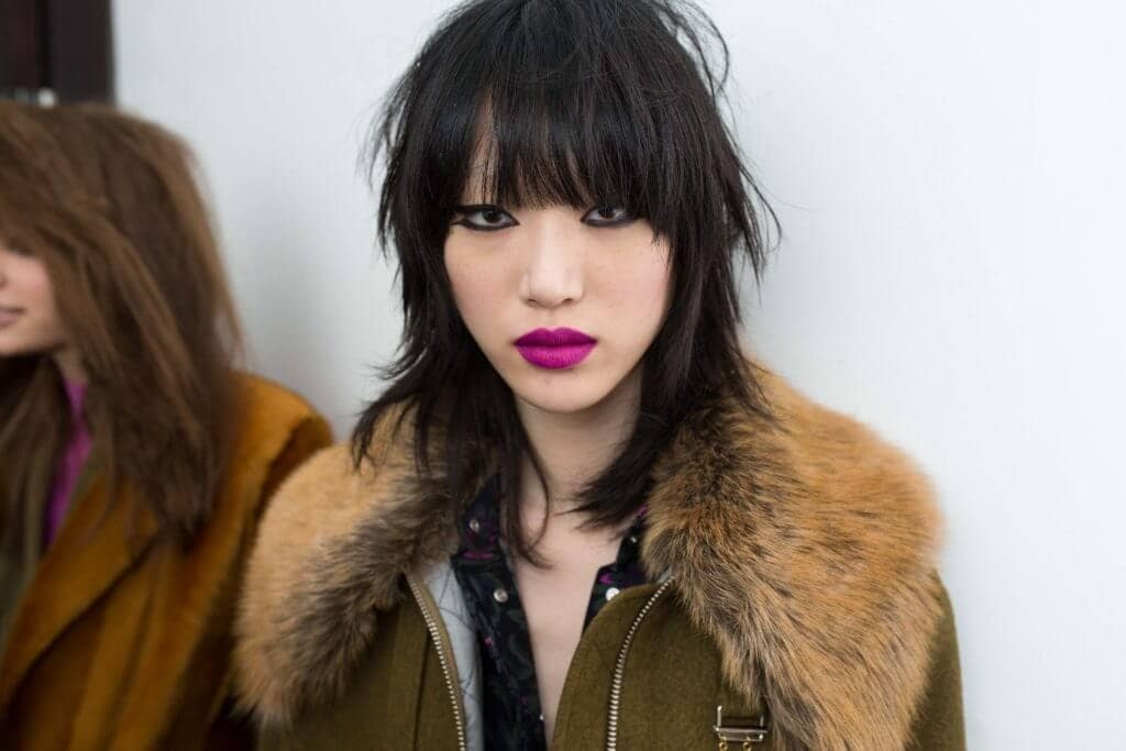model with black hair and a shag choppy bob cut and bangs