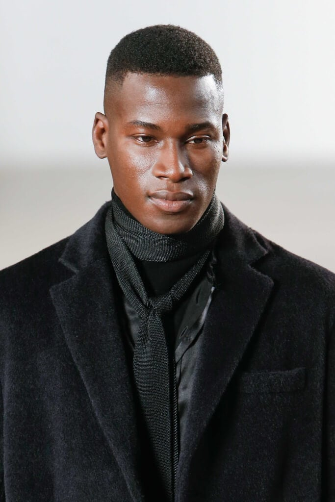 male model on the runway wearing an all black outfit with his afro hair worn high and tight