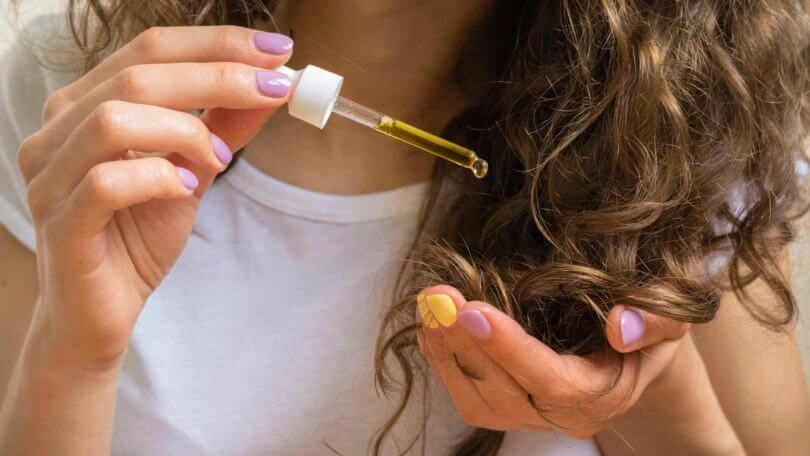 curly haired girl using hot oil treatment for hair