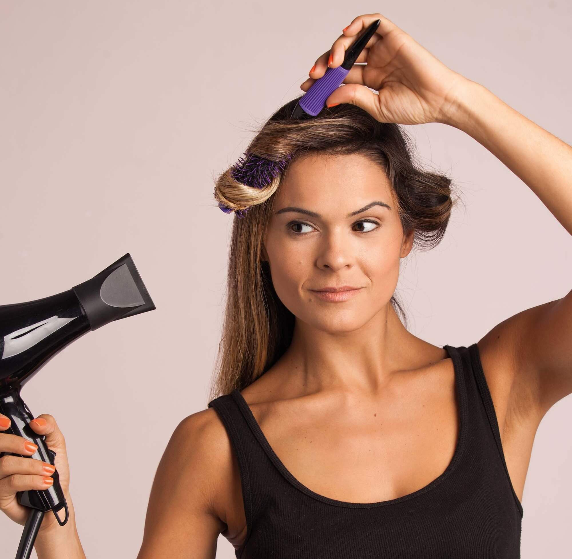how to get great blow dried hair at home woman using hair dryer and brush