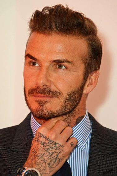 David beckham with a quiff hairstyle wearing a suit