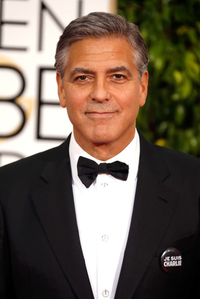 George Clooney on the red carpet with a grey quiff in a tuxedo