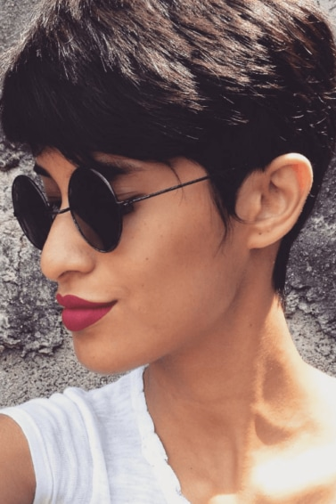 side view of a woman with dark brown hair worn in a sweeping pixie cut and wearing round sunglasses