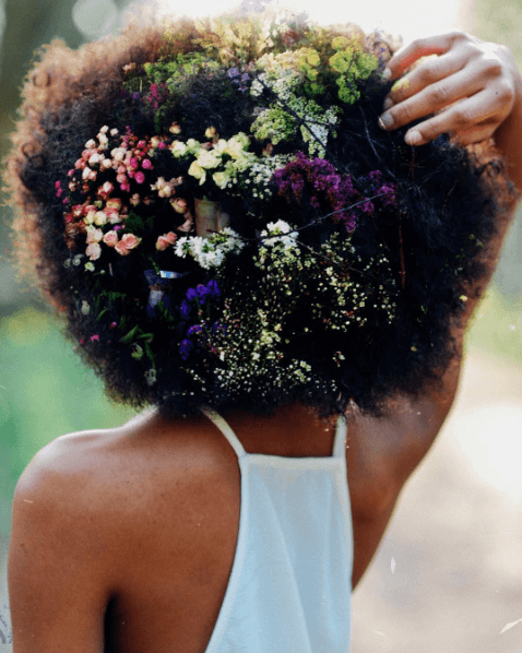 Hair Trends: Woman with natural afro hair covered with flowers.