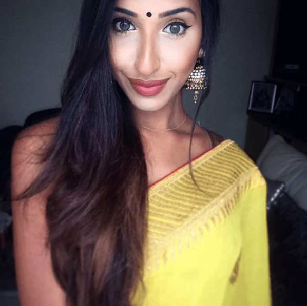 Indian hairstyles: Woman with blown out long dark brown hair with layers, wearing a yellow sari with drop earring posing in a bedroom