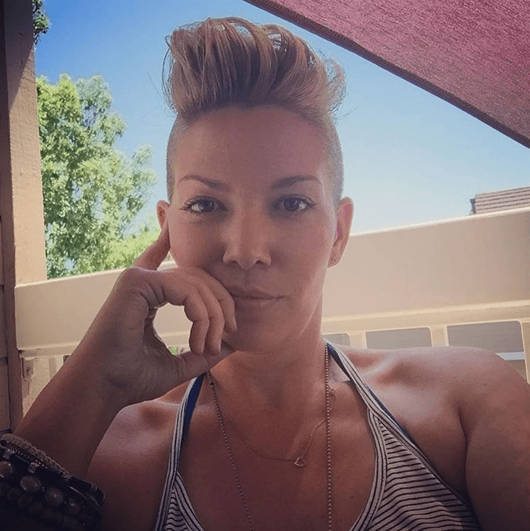 woman with blonde hair cut into a mohawk pixie with shaved sides