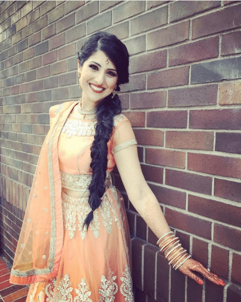Indian hairstyles: Woman with dark brown long hair styled into a side fishtail plait, wearing orange sari posing outside