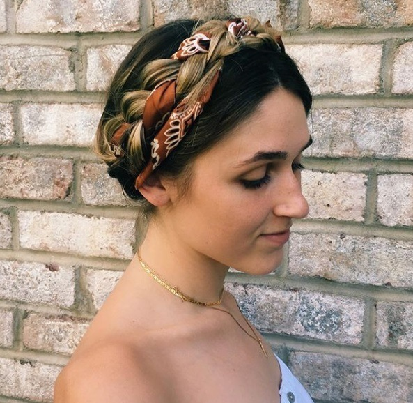 Updos with braids: Close up shot of a woman with caramel brown hair styled into a milkmaid braid updo with a scarf accessory.