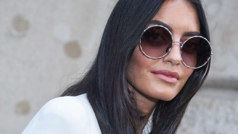 keratin treatment: close up shot of woman with dark smooth hair, wearing sunglasses with a white top, and posing for a street style shot
