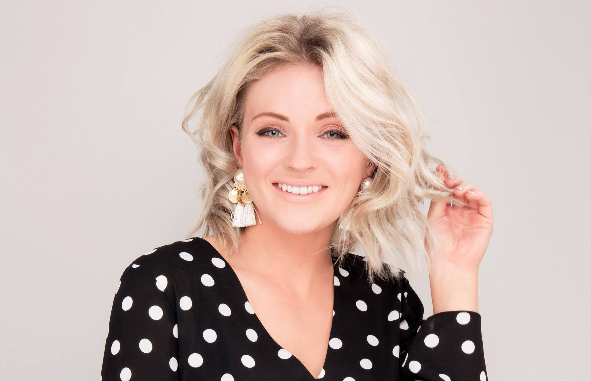 How to use volumising spray: Blogger/influencer Laura's Little Locket with blonde bob length curly hair wearing a black and white spotty blouse