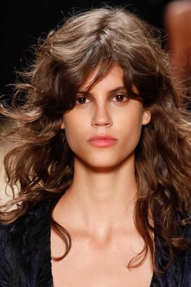 Medium length hairstyles for fine hair: Woman with brown medium length hair with messy waves and side fringe on runway.