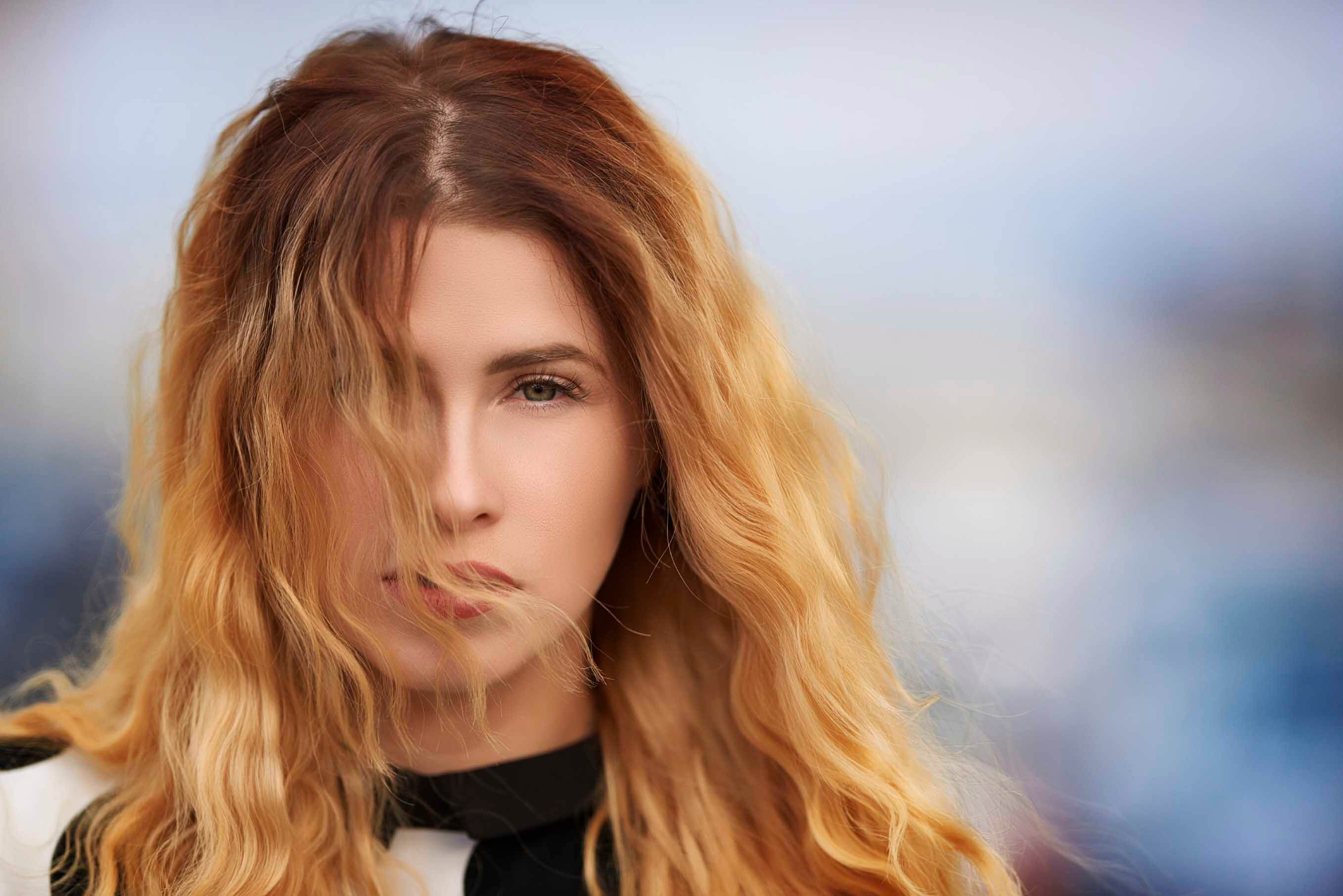woman with long wavy orange ombre hair