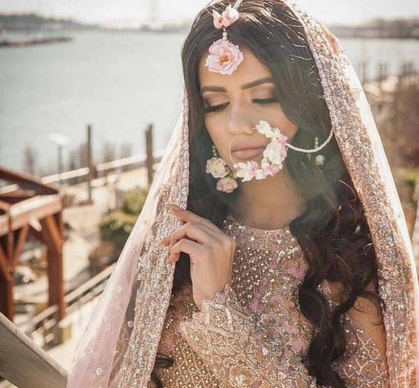 Indian hairstyles: Woman with long, dark loose curls wearing a sari over her head with a hair tikka and nose ring jewellery