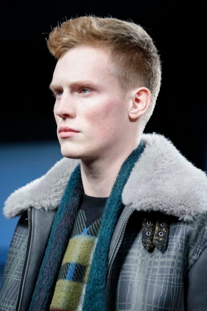 male model on the runway wearing a shearling jacket with a knitted sweater and scarf with his blonde hair styled into a low fade