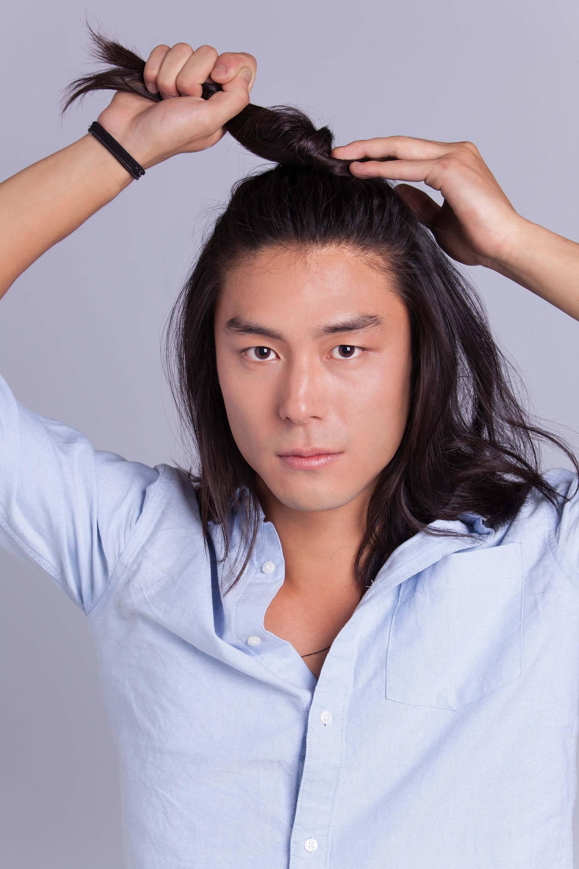 Asian man bun: Asian male model with shoulder-length hair twisting his hair into a half-up man bun