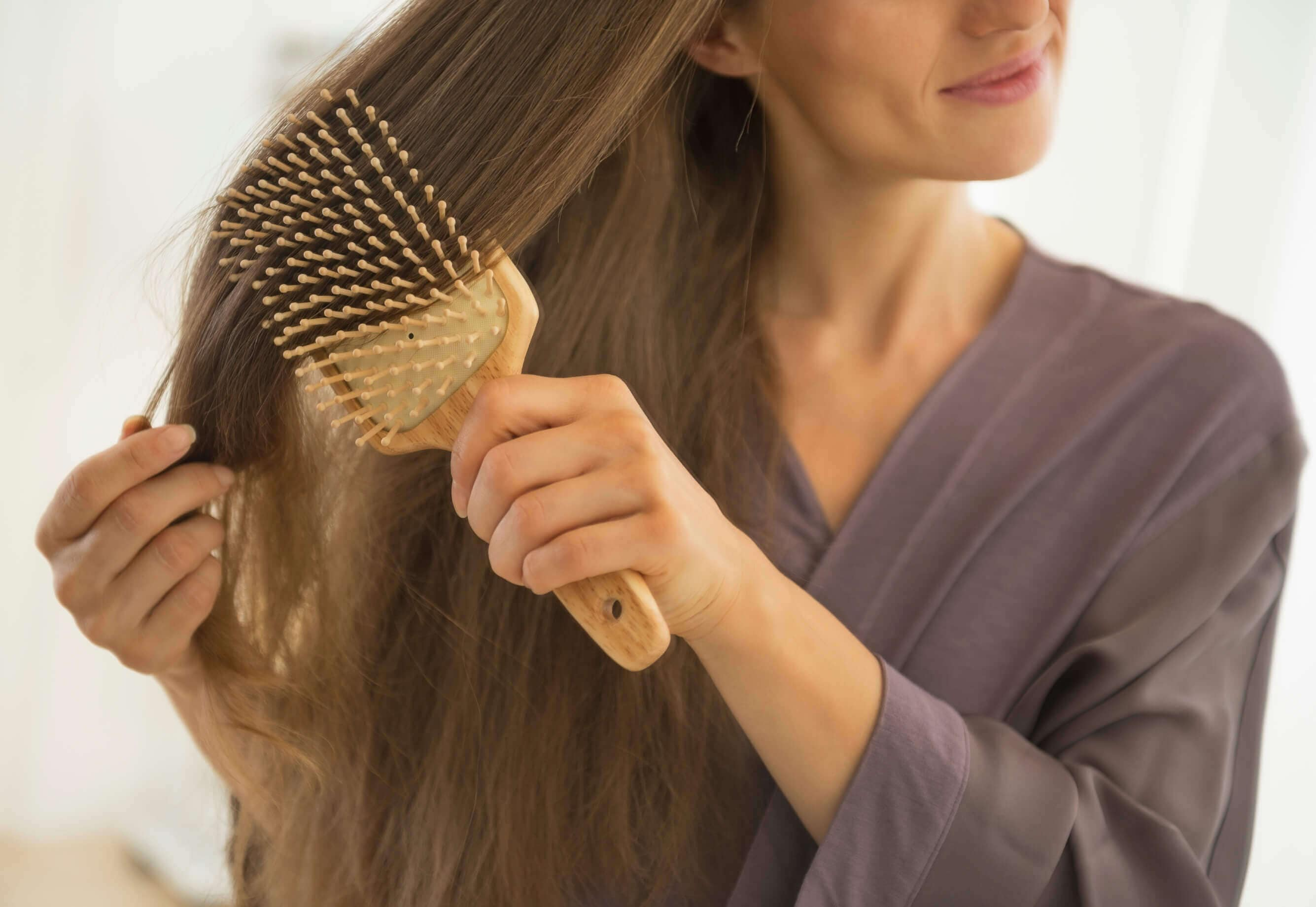 Woman brushing her hair with a brush