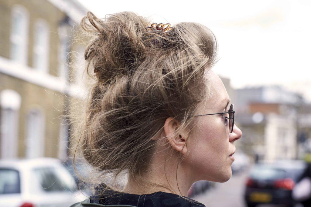 Easy hairdos for long hair: A young woman with a messy bun wearing sunglasses