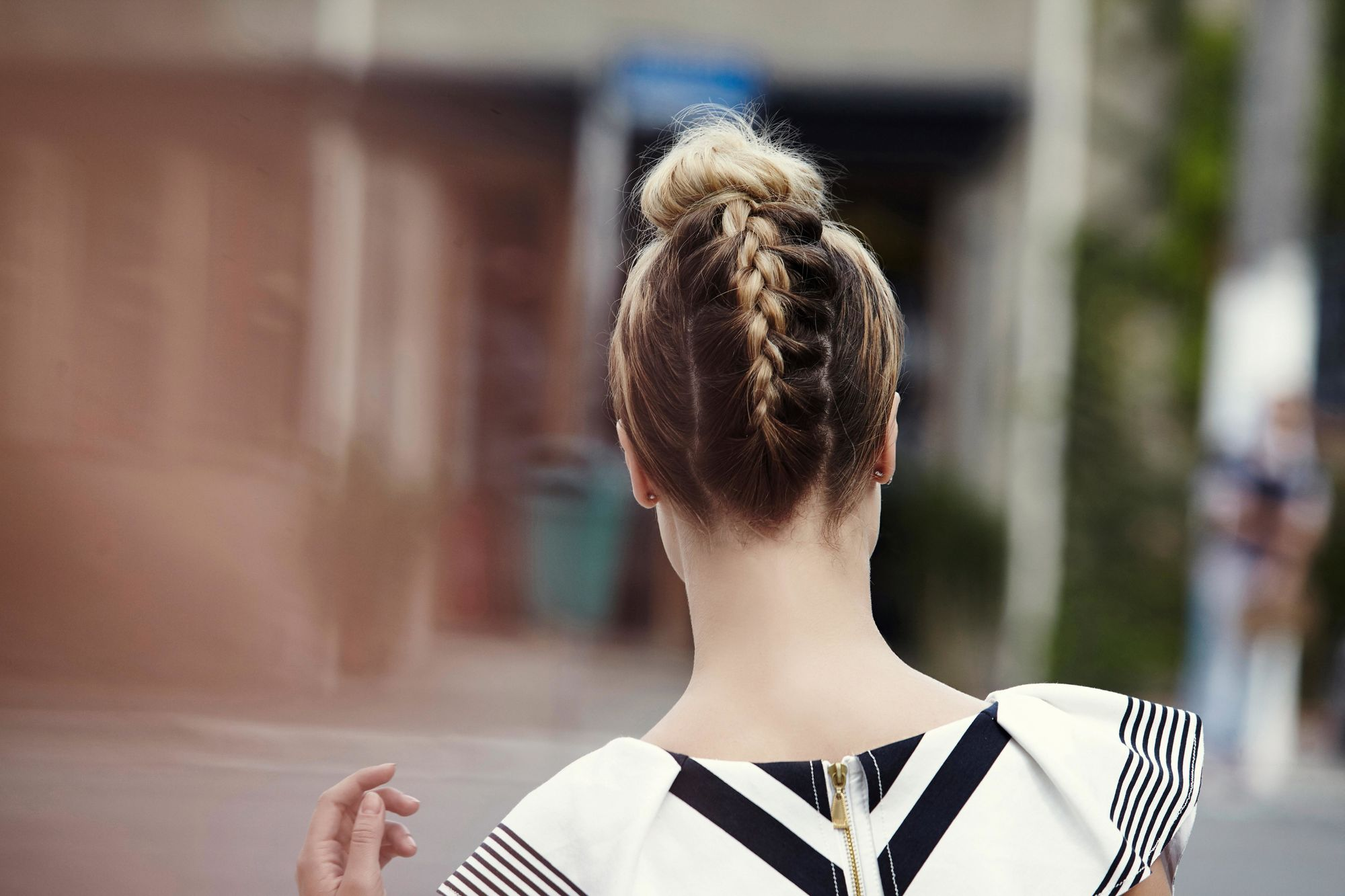 French plait styles: Back view of a blonde woman with an upside down French plait bun