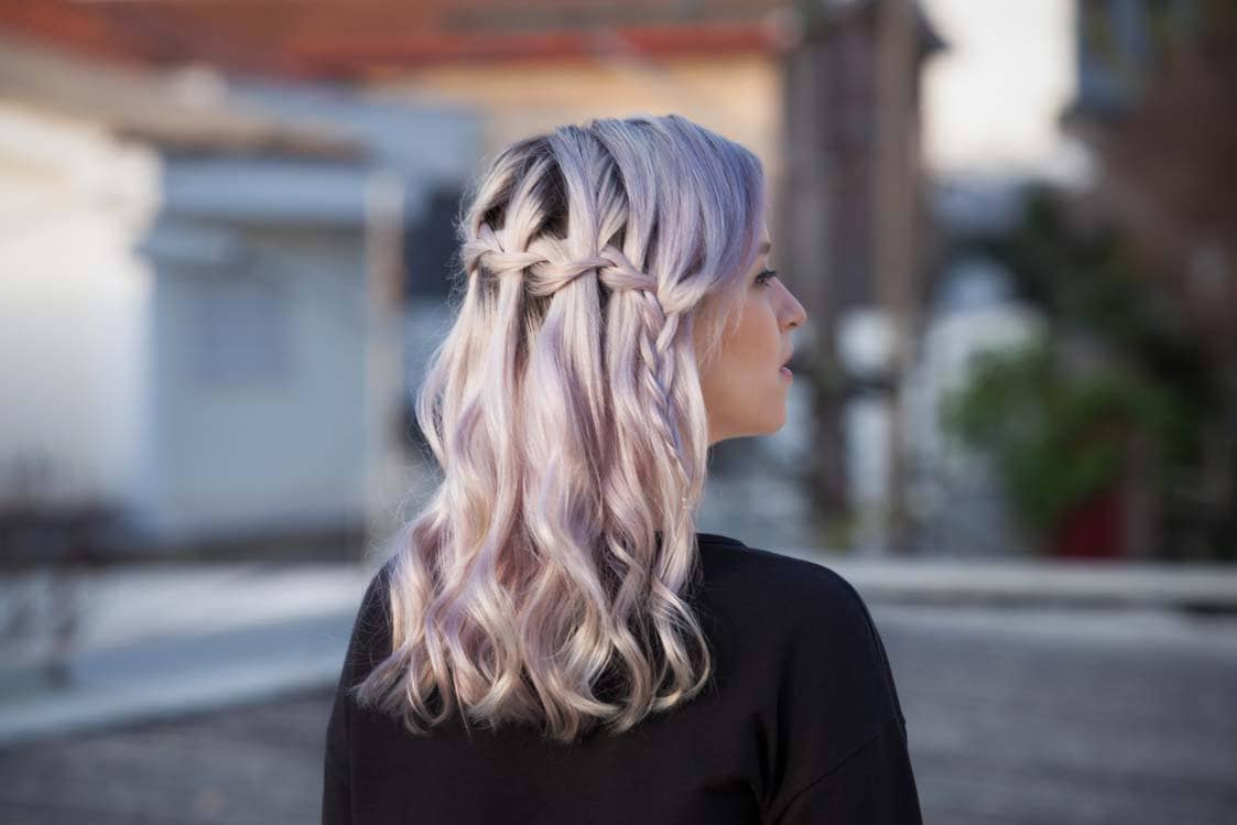 model with pastel pink hair in a waterfall braid half up half down curly hairstyle