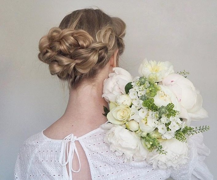 Updos with braids: Back shot of a woman with bronde hair styled into a low pull through braided bun.