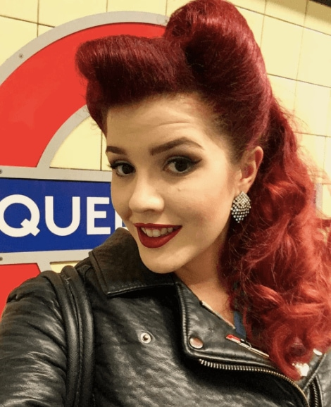 Pin up hairstyles: Front facing view of a woman with red hair in vintage victory rolls standing at a tube station