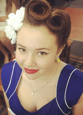 Pin up hairstyles: Front facing image of a woman with brown hair victory rolls hairstyle with a white flower
