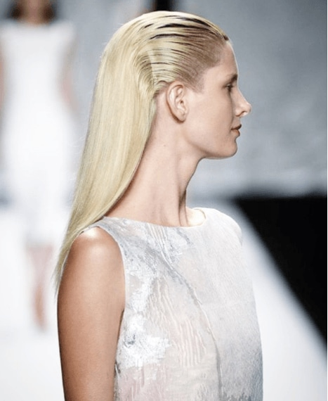 Night out hairstyles for long hair: Model with long blonde hair slicked back, wearing white and posing on the runway