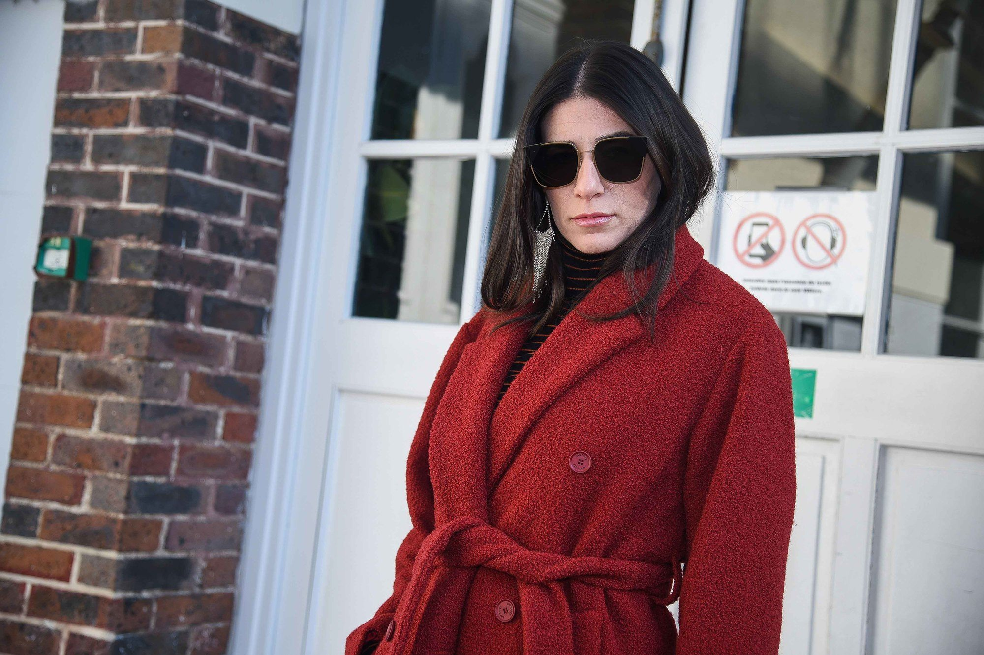 brunette street style model with sleek bob hair wearing a red tie coat