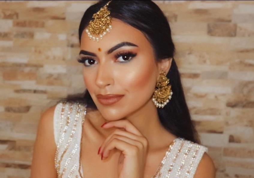 Indian hairstyles: Woman with long dark brown hair styled into a straight half-up, half-down wearing it with a hair tikka and matching earrings