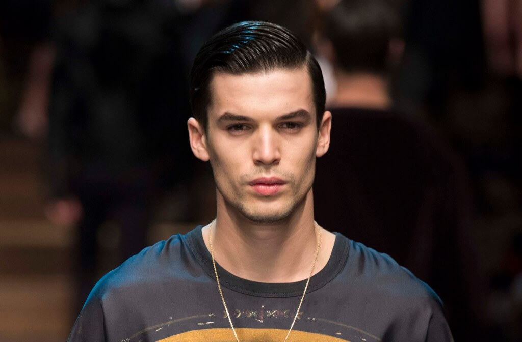 male model on the runway wearing a printed tshirt and necklace with his dark hair worn in a deep side parting and slicked back