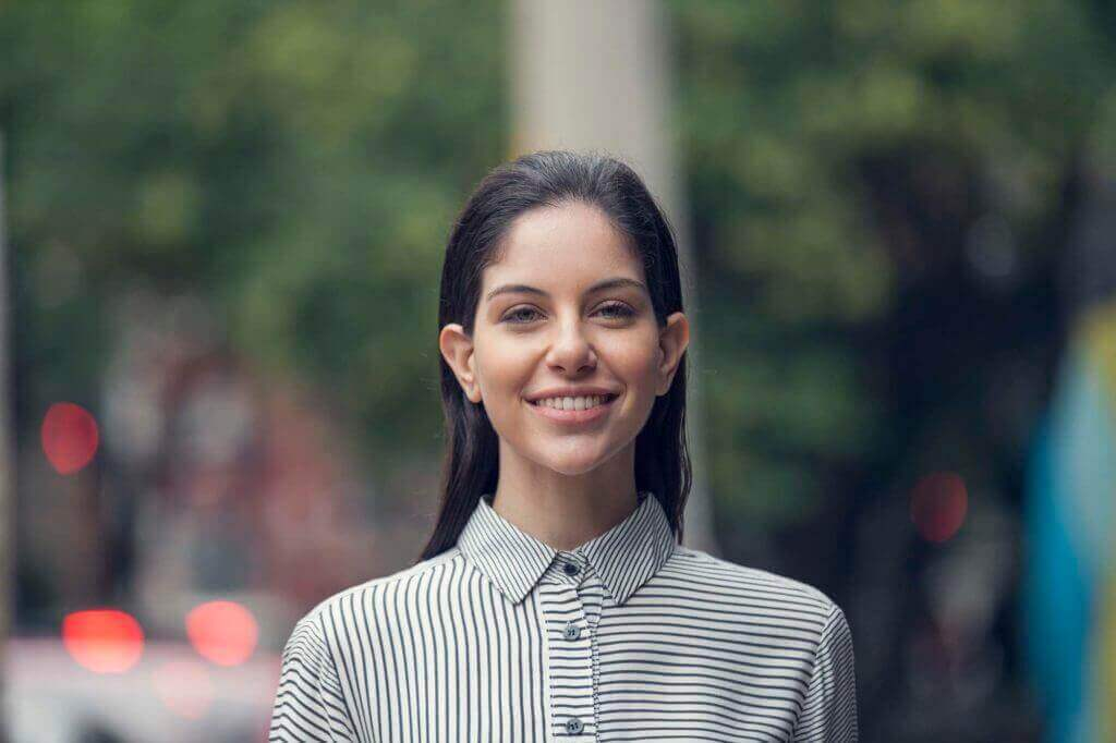 Easy night out hairstyles: Woman with dark brown slicked-back hair wearing striped shirt, posing outside