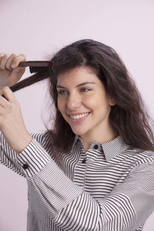 a curly woman smiling while combing her hair forward