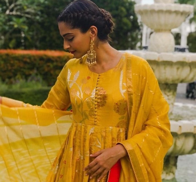 Indian hairstyles: Woman with dark brown hair styled into a French braided bun, wearing yellow sari with drop earrings outside