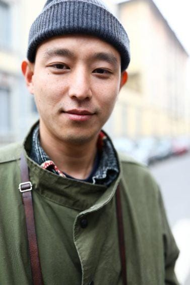 Asian men hairstyles: A young Asian man wearing a ribbed beanie hat