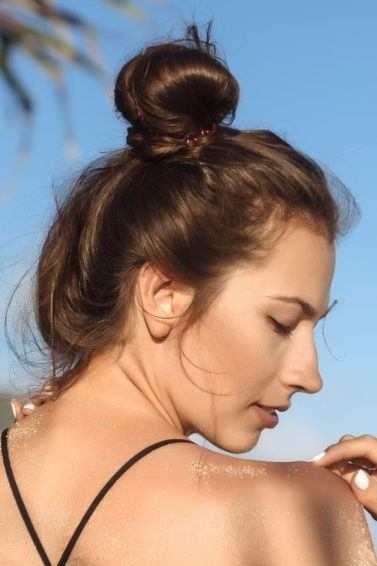 summer hair tips: close up shot of woman on the beach with dark brown hair fashioned into a bun, wearing a bikini top and posing
