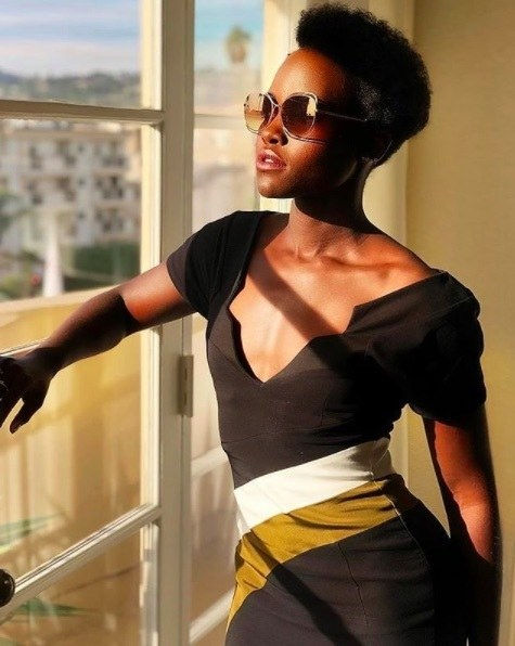 Hair trends: Lupita nyongo with short afro hair wearing sunglasses looking out of the window.
