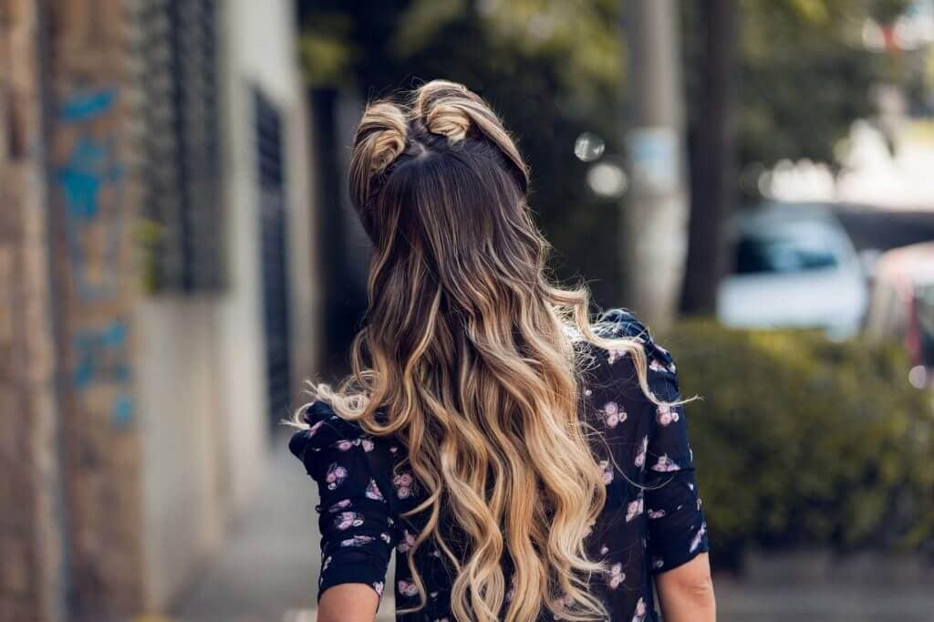back view of model with long ombre hair in curls and victory rolls