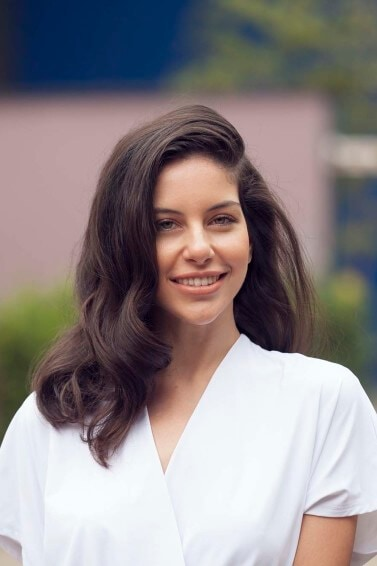 lifestyle shot of a brunette model with shoulder length vintage curls with a side parting wearing a white v neck top
