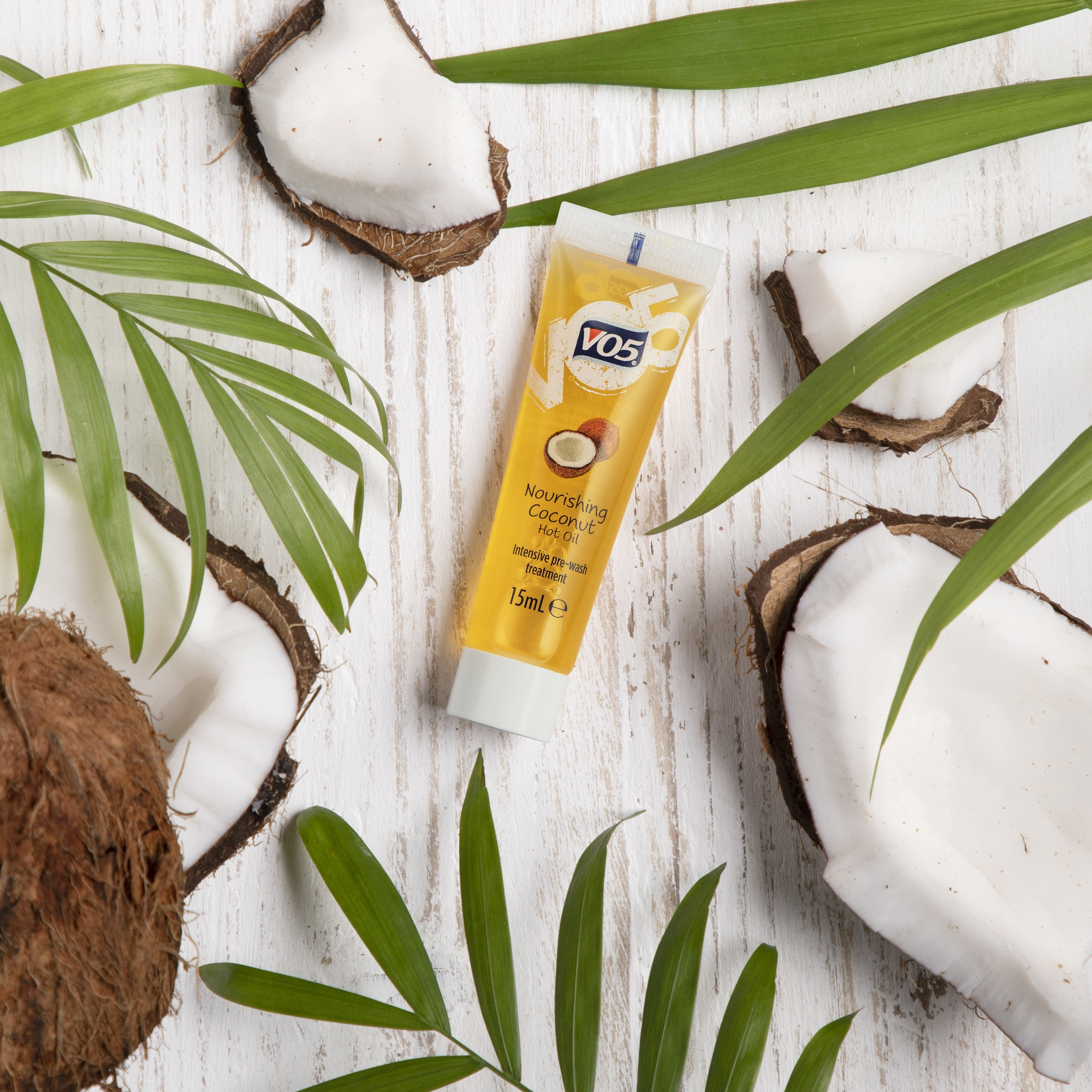 VO5 hot oil: Flat lay of the new VO5 Nourishing Coconut Oil on a white wooden background decorated with coconuts and palm tree leaves