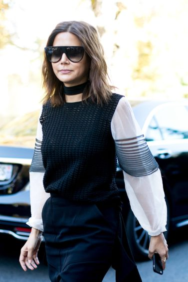 woman on the street wearing large sunglasses with her medium brunette hair cut into a wavy bob