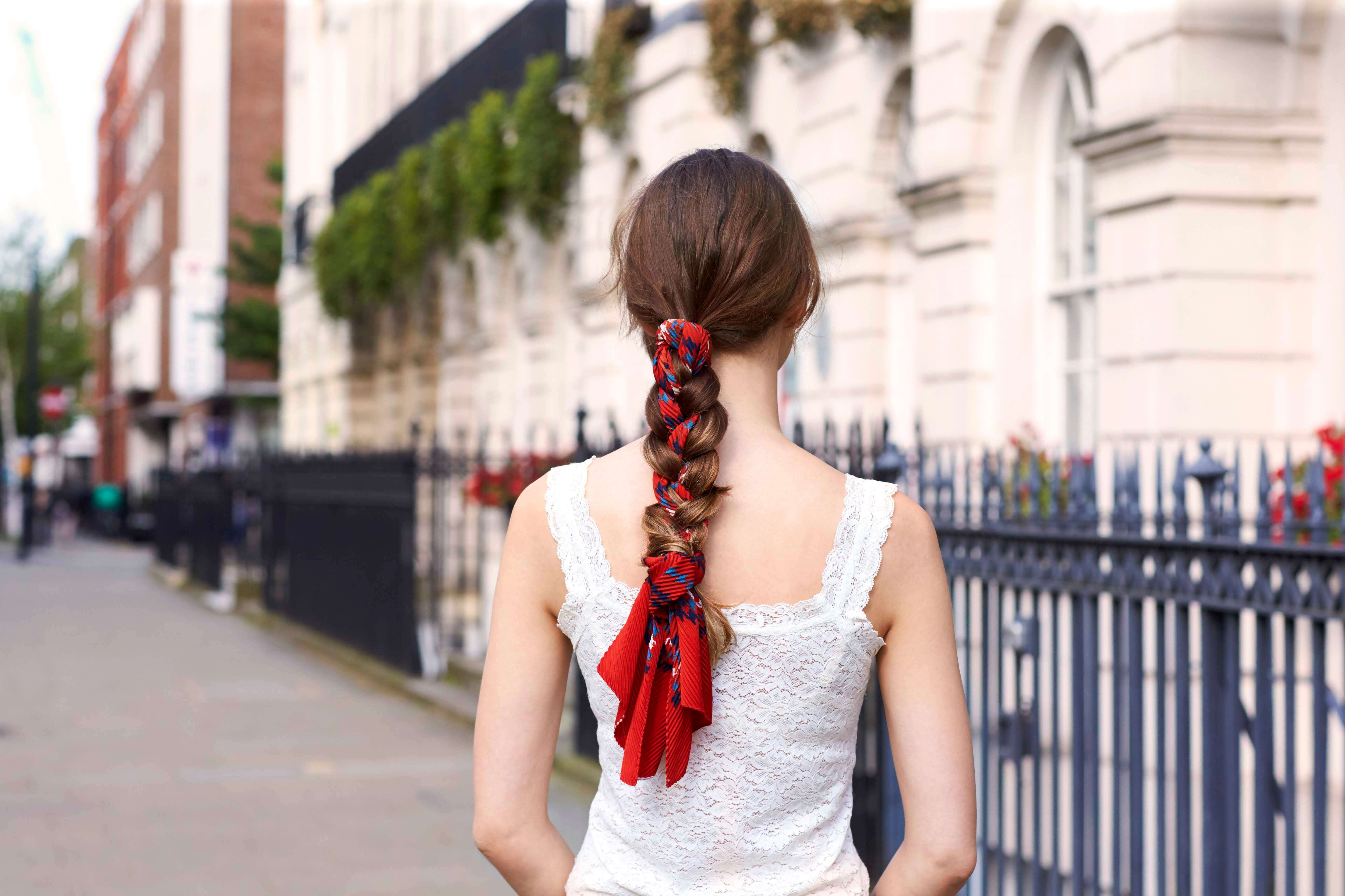 back view of woman with interwoven red scarf braid