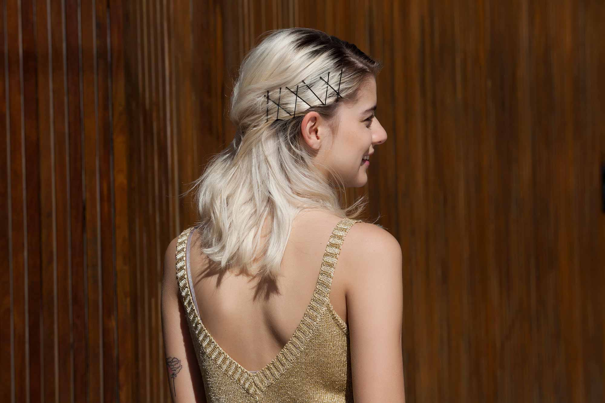 Bobby pin hairstyles: Close up shot of a woman with bleach blonde half up half down hairstyle with bobby pins