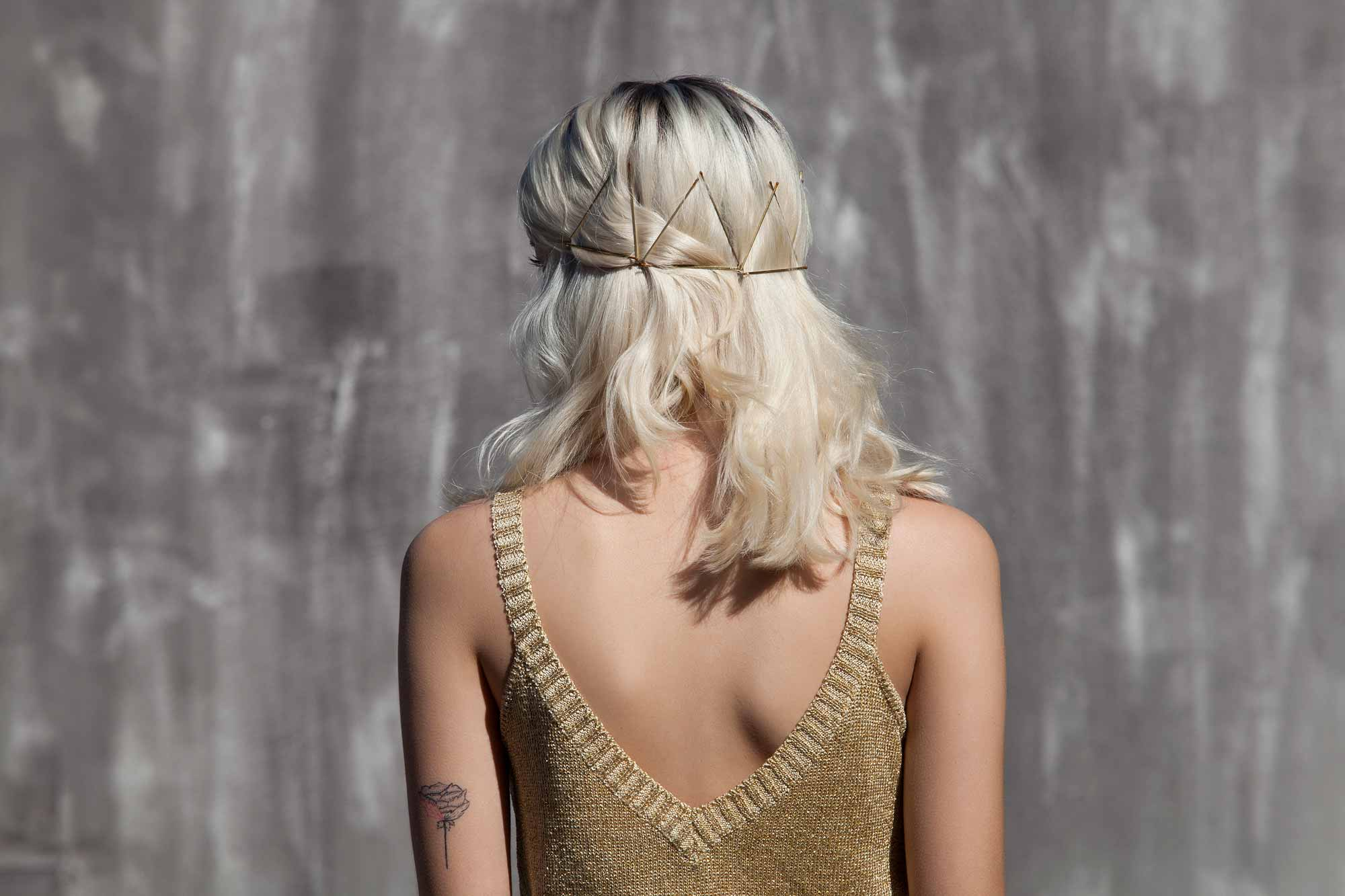 Bobby pin hairstyles: Close up backshot of a woman with messy bleach blonde medium hair styled with a triangle bobby pins, wearing a gold top and posing outside
