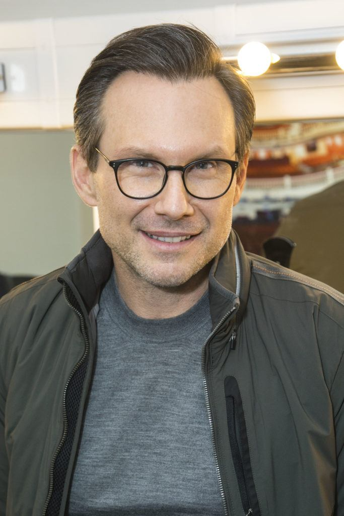 Christian Slater wearing glasses with slicked back hair
