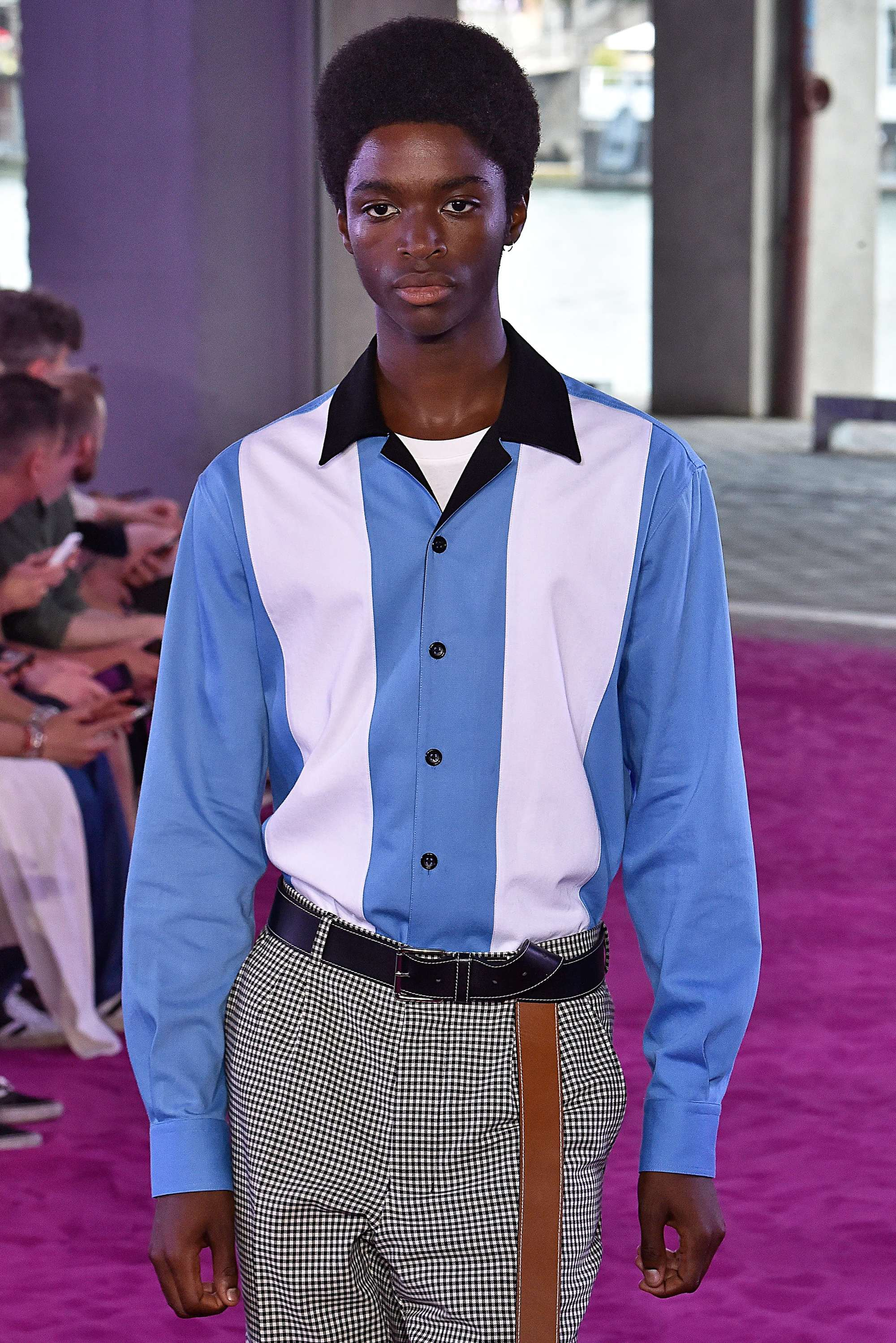 close up shot of black man with rounded power afro, wearing striped shirt and checked trousers on the AMI ss18 runway